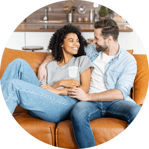 Image of a couple sitting on a brown couch together and smiling at one another. This couple represents the many who find support from a premarital counselor in Louisville, CO. Start premarital counseling in Louisville, CO today.   80305   80403