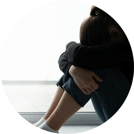 Image of a young woman sitting with her head between her knees. This image is illustrative of how someone experiencing symptoms of trauma may feel. You can treat symptoms of trauma in EMDR therapy in Louisville, CO. 80304 | 80303 | 80301