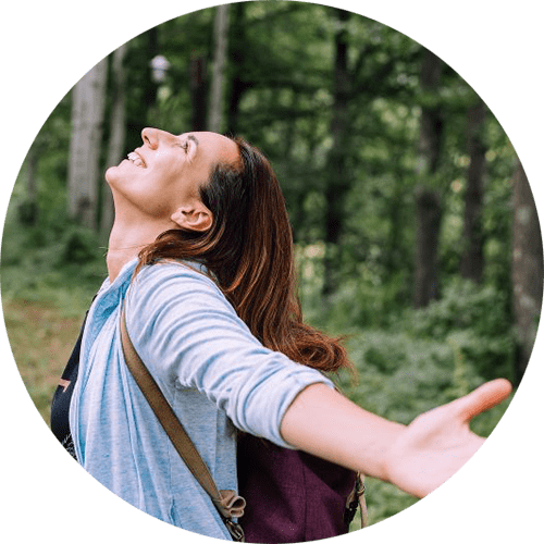 Image of a woman holding her arms out and smiling at the sky while standing in the woods. This image represents what a woman may look like after meeting with an anxiety therapist in Louisville, CO to learn about overcoming perfectionism. | 80027 | 80025