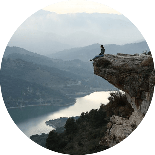 Image of a person sitting on the edge of a cliff overlooking a river and mountains. This image illustrates how isolating life changes can be. But seeing a therapist for therapy for life transitions in Louisville, CO can help.   80305   80403