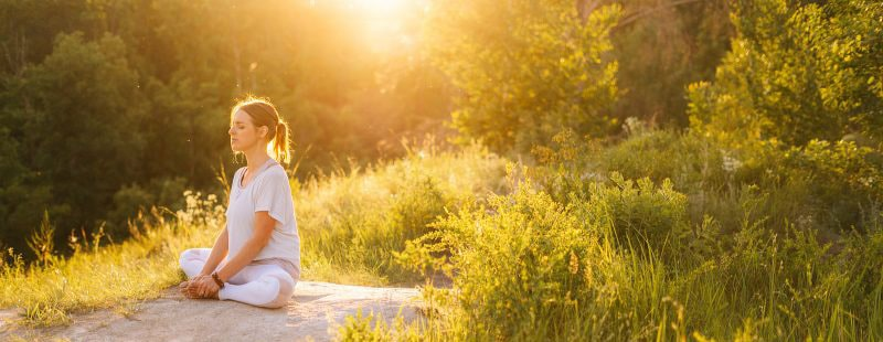 Image of a woman sitting peacefully on a large rock in the middle of a field of green bushes. This image illustrates the peace women can find after anxiety treatment in Louisville, CO. Working with an anxiety therapist can help with overcoming perfectionism. | 80305 | 80403