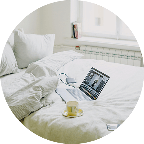 Image of a bed with a coffee cup and laptop resting on it. This image represents what someone's set up for online therapy in Louisville, CO sessions may look like. You can get support from an online therapist in Louisville, CO here. 80027