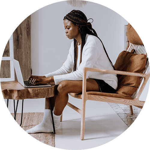Image of a woman sitting in a chair and using a laptop. This image illustrates what someone meeting with an online therapist in Golden, CO may look like. Starting online therapy in Colorado from Golden, CO can help with anxiety and couples issues like communication problems. | 80403