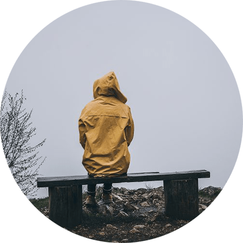 Image of a person wearing a yellow rain jacket sitting on a bench alone. This photo illustrates how lonely someone may feel before doing EMDR therapy in Louisville, CO. 80516 | 80007