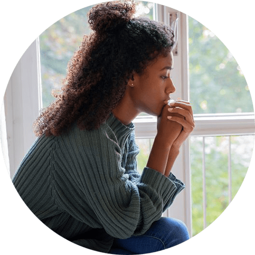 Image of a young woman sitting with her hands on her chin. This image represents how a sexual assault survivor may feel before therapy for sexual assault in Louisville, CO. 80305   80403