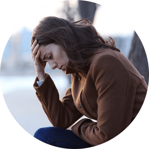 Image of a woman wearing a brown coat sitting outdoors with her hand held to her forehead. This image depicts how many women feel before working with an anxiety therapist in Louisville, CO for anxiety treatment and overcoming perfectionism. | 80304 | 80303 | 80301 | 80304 | 80303 | 80301