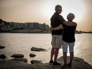 Image shows an older couple standing on rocks next to the river while embracing and looking at one another. This photo could represent a stronger bond felt after couples therapy in Louisville, CO or Boulder, CO. Seeing a couples therapist in Louisville, CO can teach many tools in couples therapy and marriage counseling in Boulder, CO, Denver, CO and Louisville, CO. | 80027 | 80026 | 80020