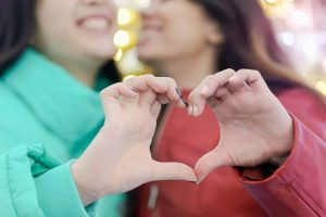 Photo shows two women making a heart shape with their hands while smiling at each other. This image could represent a couple seeing a couples therapist in Louisville, CO. Couples therapy in Louisville, CO, and Boulder, Denver and online therapy in Colorado can help strengthen relationships. | 80027 | 80026 | 80020