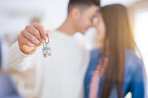 Image shows a young couple embracing and smiling as they hold out a key to their home. This photo could represent the happiness felt by the couple despite being in couples therapy in Louisville, CO. Seeing a couples therapist near Louisville, CO or Boulder, CO can help strengthen any relationship. | 80027 | 80304 | 80303 | 80301