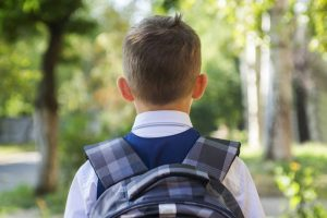 Child walking to school with backpack. Life transitions are hard for co-parenting in Louisville, CO and beyond. Get help with co-parenting tips in Boulder County, CO from an online therapist in Colorado here.