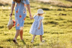 Mother and daughter walking in a field, hand-in-hand. Co-parenting help in Louisville, CO with a therapist in Boulder County, CO can help you with co-parenting and this difficult time of life transitions in Boulder County, CO. Get online therapy in Colorado here!